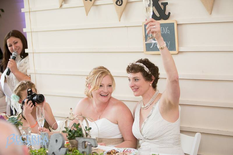 2 brides raising a toast