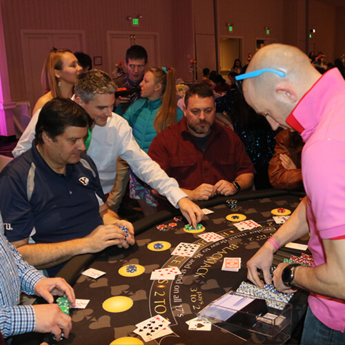 A Fallon Love poker dealer with a full table of players.