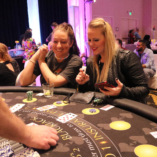 women playing blackjack at a casino event.