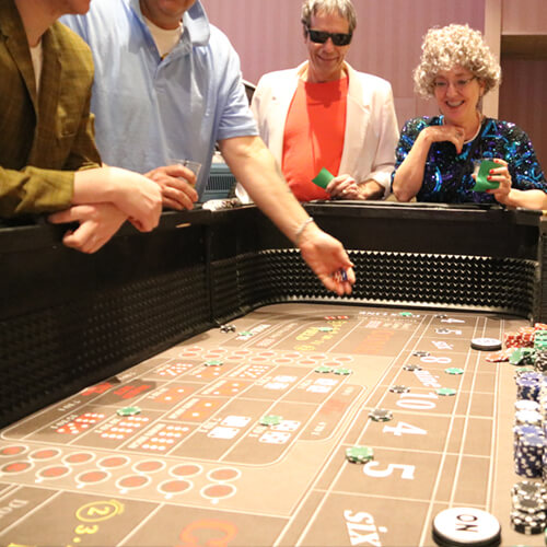 A group of party goers playing craps.