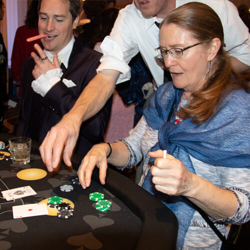 a woman collecting her winnings playing blackjack at a casino party.